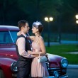 Pretty couple near the vintage car on the night city background — Stock Photo #67767925