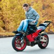 Постер, плакат: Stunt rider is riding motorbike without feet