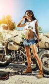 Sexy mechanic girl is repairing old motorbike. — Stock Photo