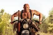 Muscular bald biker on the autumn background. Instagram-like ton — Stock Photo