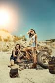 Sexy mechanic girls are repairing old motorbike on the desert ba — Stock Photo