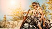 Sexy couple of bikers with guns on the summer background. — Stock Photo