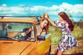 One woman is trying to pull another out of the car. — Stock Photo