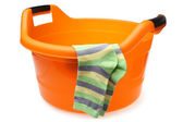 Orange plastic wash bowl with striped socks — Stock Photo