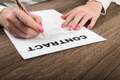 Businesswoman's hands signing contract. — Stock Photo