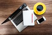 Office desk with laptop computer and coffee cup — Stock Photo