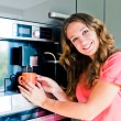 Happy young woman making coffee cup machine kitchen interior — Stock Photo #60402109