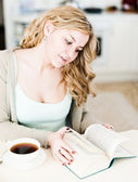 Beautiful woman reads an interesting book and drinks coffee — Stock Photo