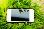 Mobile phone in grass — Stock Photo