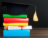 A mortarboard and graduation scroll on books — Stock Photo