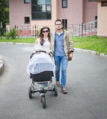 Happy man and woman walking with baby pram outdoors — Stock Photo