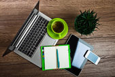 Office desk with laptop and cup of tea — Stock Photo