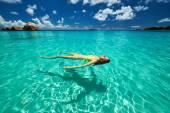 Woman in yellow bikini lying on water  — Stock Photo