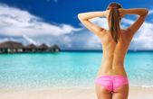 Woman topless on beautiful beach with water bungalows — Stock Photo