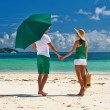 Couple in green with umbrella — Stock Photo #73533727