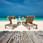 Pareja en blanco relajarse en la playa — Foto de Stock   #74763219