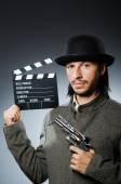 Man with gun and movie clapboard — Stock Photo