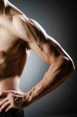 Muscular man posing in dark studio — Stock Photo