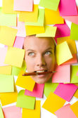 Woman with many reminder notes and pen in the mouth — Stock Photo