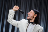 Man singing in front of curtain in karaoke concept — Stock Photo