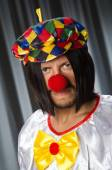 Sad clown against grey background — Stock Photo