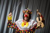 Funny clown plyaing violin against curtain — Fotografia Stock