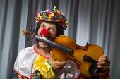 Funny clown plyaing violin against curtain — Stock Photo