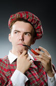 Funny scotsman smoking pipe tobacco — Stock Photo