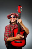 Funny scotsman playing red guitar — Stok fotoğraf