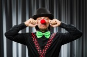 Funny clown in humorous concept against curtain — Stock Photo