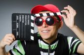 Man with baseball cap and movie board — Stock Photo