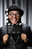 Funny man with movie board against curtain — Stock Photo