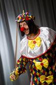 Funny clown plyaing violin against curtain — ストック写真