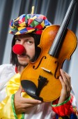Funny clown plyaing violin against curtain — Stok fotoğraf