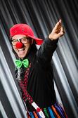 Funny clown in humorous concept against curtain — ストック写真
