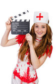 Woman doctor in bloody uniform with movie clapperboard — Stock fotografie