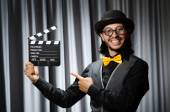 Funny man with movie board against curtain — Stock fotografie