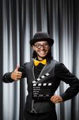 Funny man with movie board against curtain — Zdjęcie stockowe