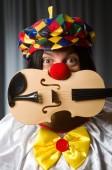 Funny clown plyaing violin against curtain — 图库照片