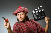 Funny scotsman with movie board and smoking pipe — Stock fotografie