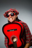 Funny scotsman playing red guitar — Stock fotografie