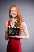 Woman in red dress with movie board — Stock Photo