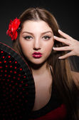 Beautiful young woman with flower and fan — Stock Photo