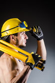 Ripped muscular builder man with tools — Stock Photo