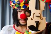 Funny clown plyaing violin against curtain — Stock Photo