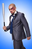 Badly bruised businessman with bat — Stock Photo
