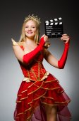 Queen in red dress with movie clapboard — Stock Photo