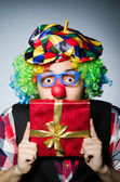 Funny clown with red giftbox — Stock Photo