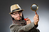 Funny detective with smoking pipe and magnifying glass — Stock Photo