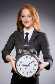 Businesswoman with clock being late for her deliverables — Stock Photo